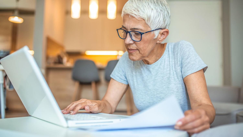 Frau gleicht Informationen auf einem Blatt Papier mit Daten auf ihrem Computer ab.