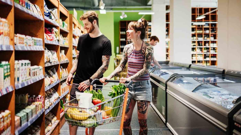 Ein junges, tätowiertes Paar steht mit einem gefüllten Einkaufswagen vor einem Supermarktregal und betrachtet die Auslage