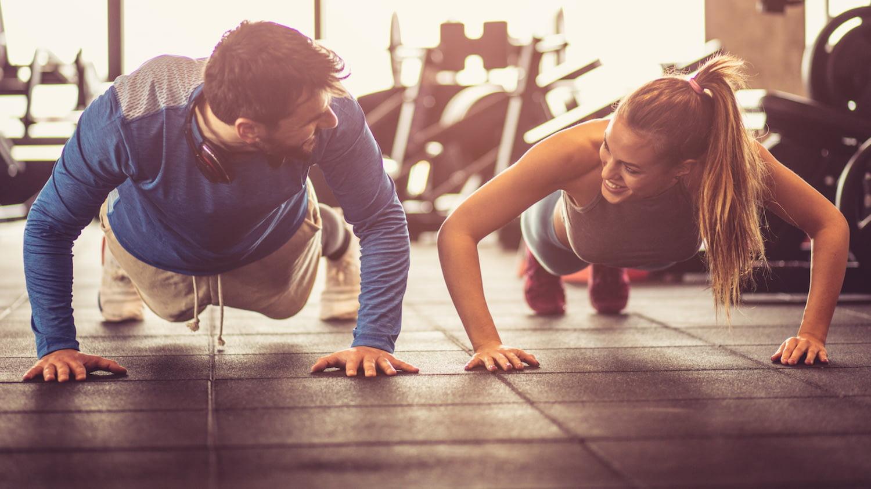 Junger Mann und junge Frau machen im Fitnessstudio nebeneinander Liegestütze