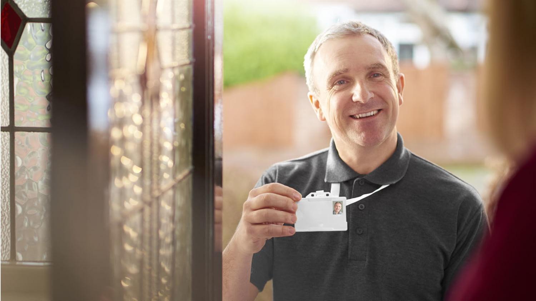 Ein freundlicher Mann mittleren Alters steht vor der Haustür und zeigt der Hausbewohnerin seinen Dienstausweis