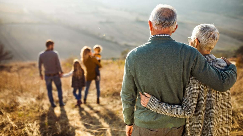 Älteres Ehepaar blickt auf seine Kinder und Enkel