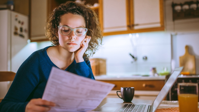 Eine Frau sitzt an einem Tisch und betrachtet besorgt ein Dokument