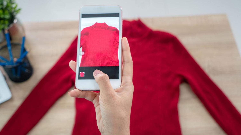 Person fotografiert mit dem Smartphone einen Pullover für den Verkauf im Internet