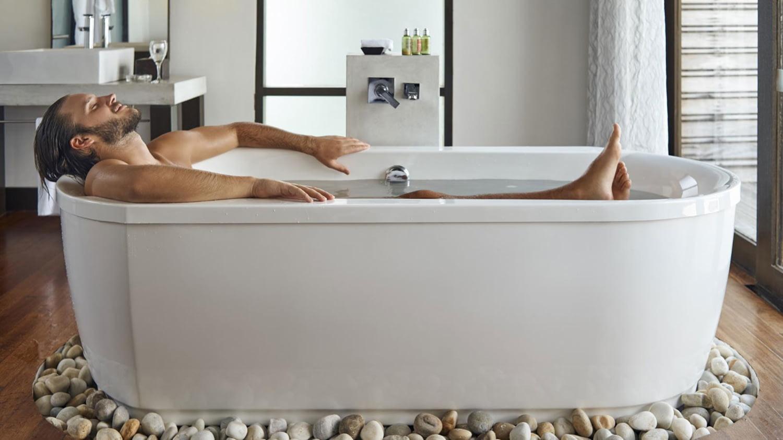 Ein Mann liegt entspannt in einer Badewanne voll Wasser