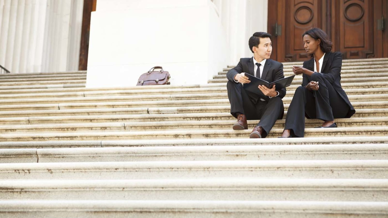 Anwältin und Klient sitzen auf einer Treppe vor einem Gerichtsgebäude
