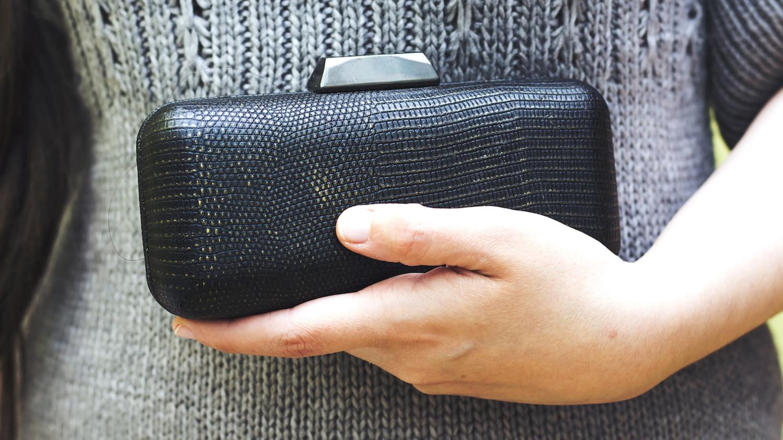 Frau im grauen Strickkleid hält eine kleine schwarze Clutch vor ihrem Bauch.