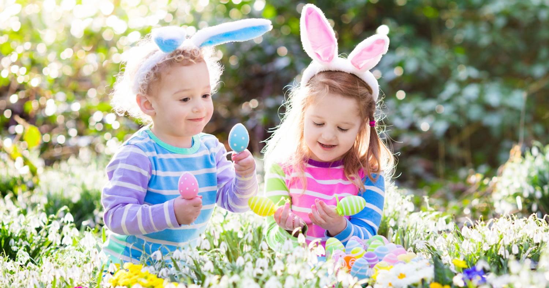 Zwei kleine Kinder mit Hasenohren-Haarreifen suchen Ostereier in einem Blumenfeld