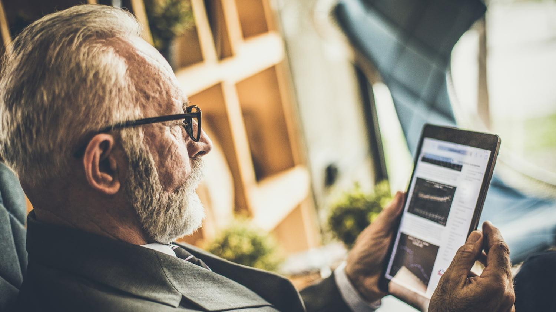 Rentenlücke schließen: Rentner betrachtet auf dem Tablet die Entwicklung seiner Geldanlage