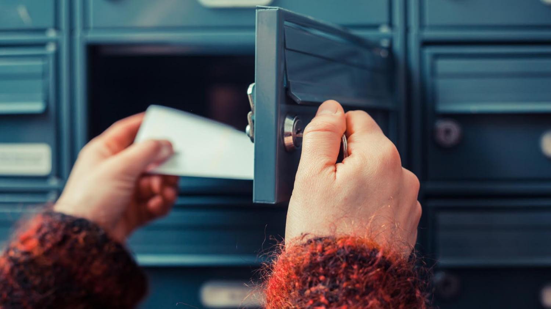 Jemand nimmt einen Brief aus seinem Briefkasten