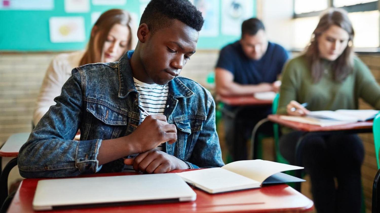 Junger schwarzer Mann schreibt eine Klausur