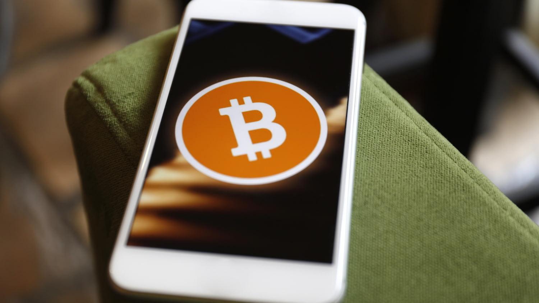 Ein Smartphone-Display zeigt das Symbol eines Bitcoins
