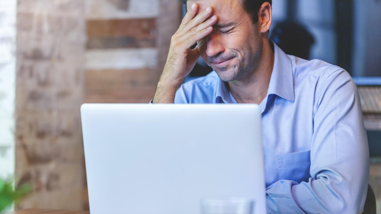 Ein Mann sitzt verzweifelt und deprimiert im Büro vor einem Laptop.