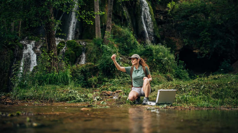 Frau nimmt Wasserprobe im Wald