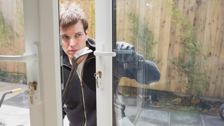 Diebstahlversicherung: Ein Einbrecher hebelt mit Brecheisen ein Fenster auf