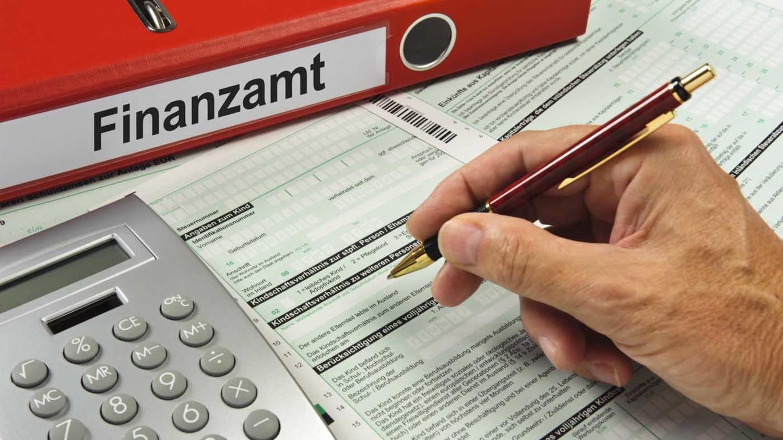 Männliche Hand füllt eine Steuererklärung aus, daneben liegen ein Taschenrechner und ein Ordner