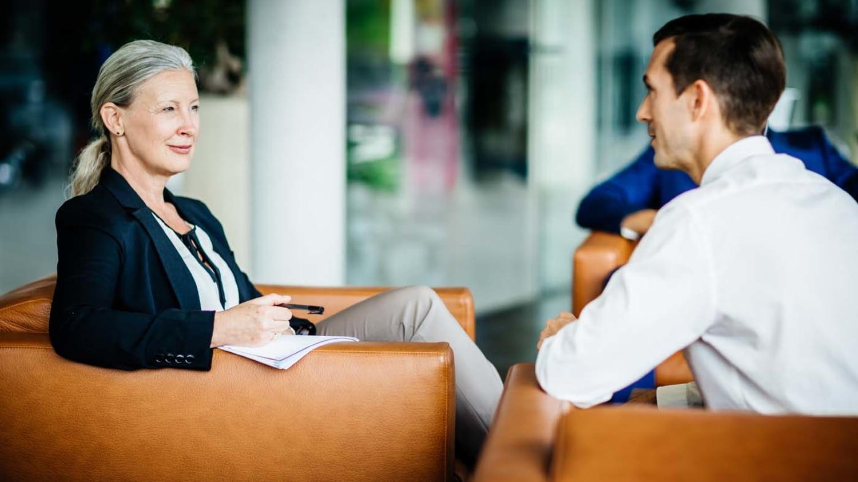 Mann und Frau sitzen sich in Geschäftssesseln gegenüber
