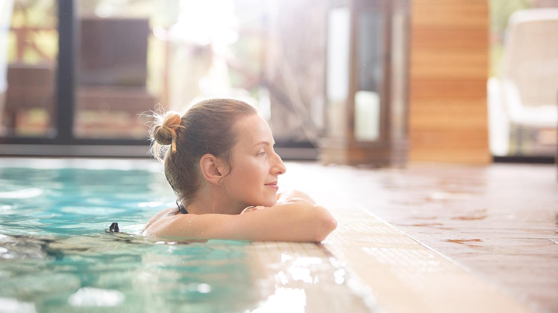 Eine junge Frau im Swimmingpool stützt entspannt lächelnd ihren Kopf mit verschränkten Armen am Beckenrand ab