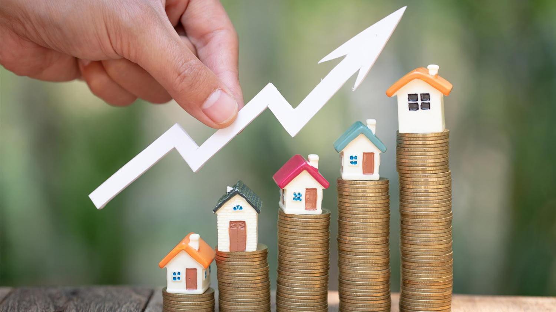 Fünf unterschiedlich hohe Münzstapel auf denen jeweils ein Modell-Häuschen steht. Darüber hält eine Hand einen aufwärts zeigenden Pfeil, der steigende Zinsen symbolisiert.