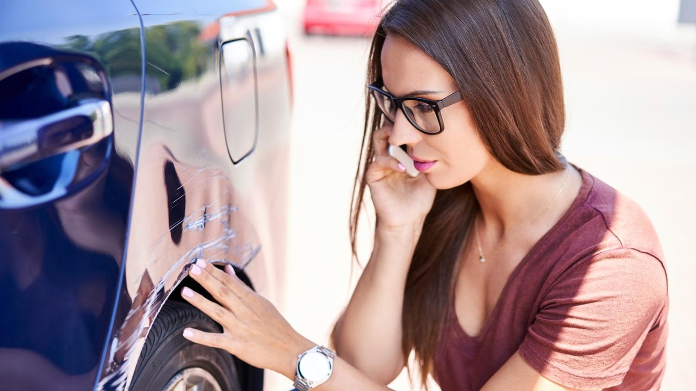Eine junge Frau fühlt über einen großen Kratzer am Kotflügel ihres Autos und telefoniert mit dem Handy