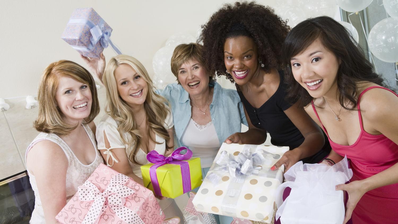 Fünf weibliche Hochzeitsgäste halten jeweils ein verpacktes Geschenk in die Kamera