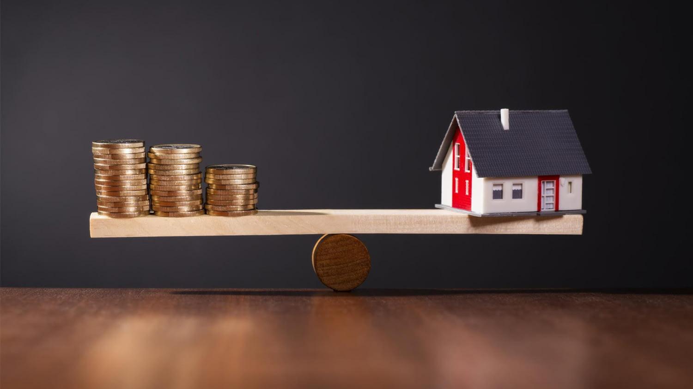 Wippe mit Geld auf der einen sowie einem Haus-Modell auf der anderen Seite