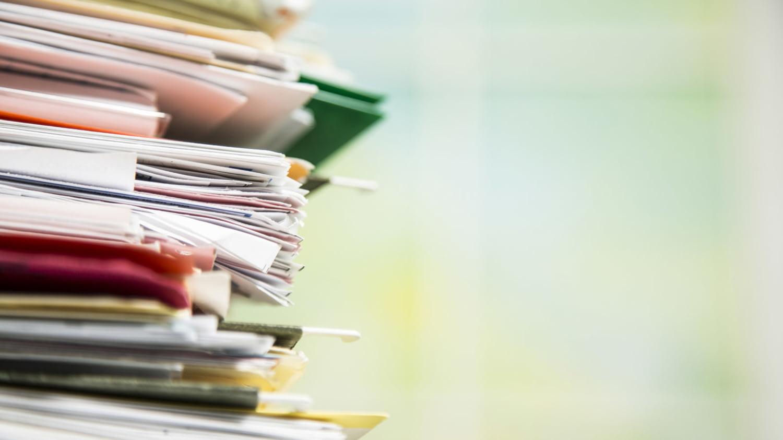 Unordentlicher Stapel aus Dokumenten, Akten und Ordnern.
