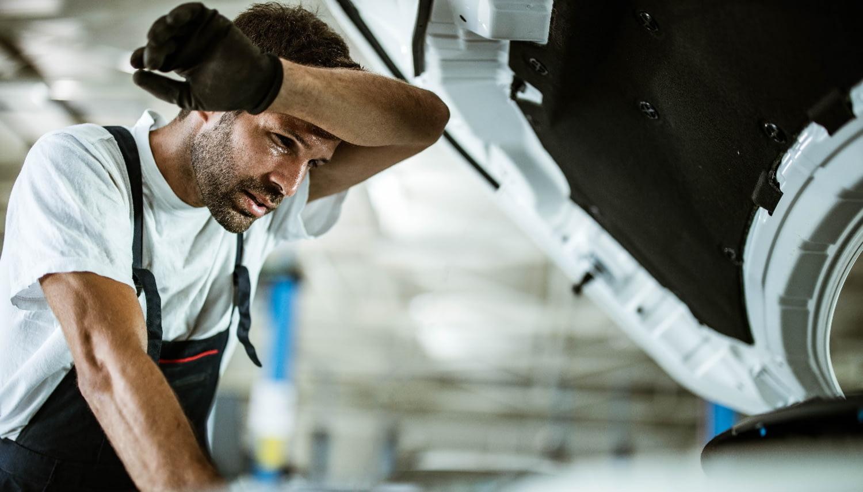 Automechaniker wischt sich den Schweiß von der Stirn