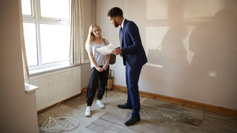 Ein Makler zeigt der Bewerberin um eine Wohnung ein Dokument