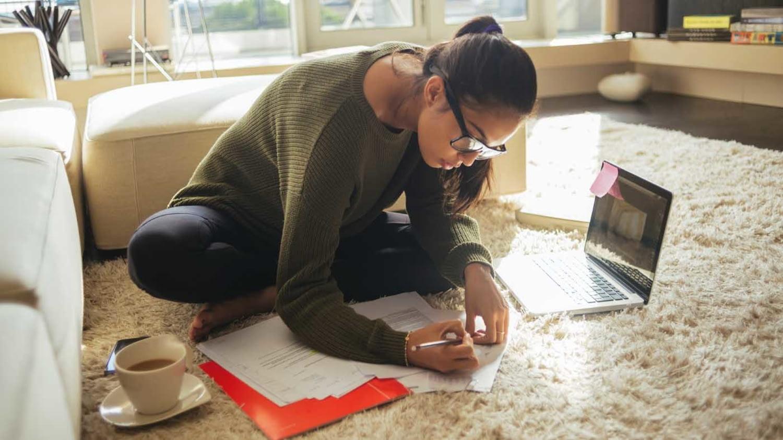 Eine junge Frau sitzt in ihrem Wohnzimmer im Schneidersitz auf dem Teppich und füllt Formulare aus