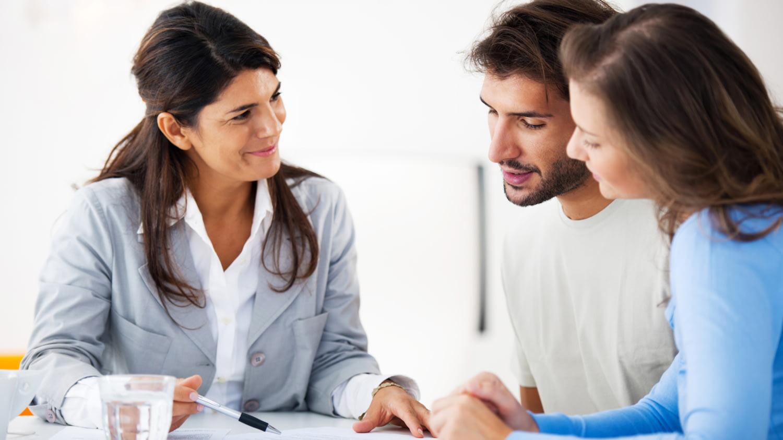 Ein junges Paar im Gespräch mit einer Kundenberaterin
