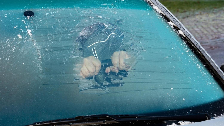 Durch eine kleine, vom Eis befreite Stelle einer Windschutzscheibe sind zwei Hände am Lenkrad zu sehen