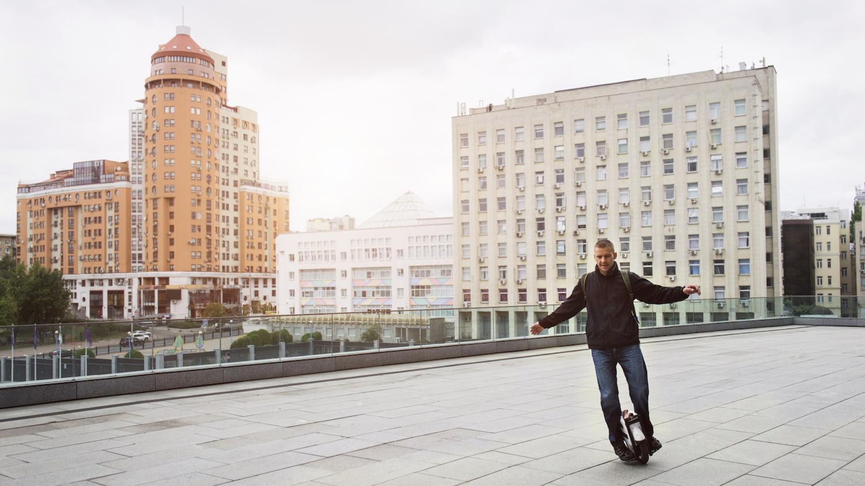 Mann auf einem E-Einrad auf einem breiten Platz, im Hintergrund eine städtische Häuserkulisse