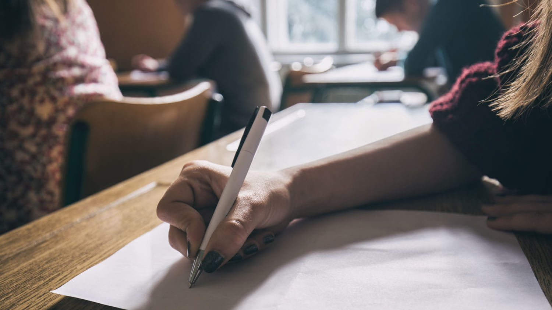 Schülerin im Klassenraum während einer Prüfung vor einem leeren Blatt Papier