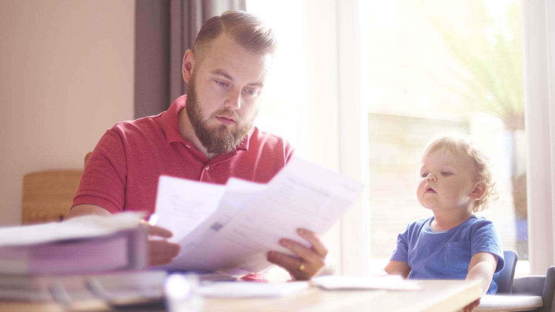 Vater sitzt mit Kleinkind an einem Tisch und blickt in Steuerunterlagen