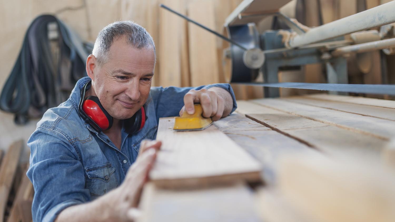 Tischler poliert eine Holzlatte in seiner Werkstatt