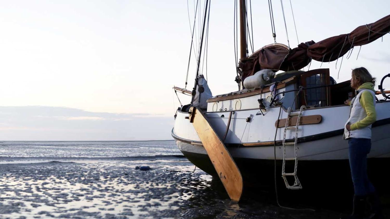 Im Wattenmeer auf Grund gelaufenes Segelboot, daneben eine Frau, die Richtung Horizont schaut