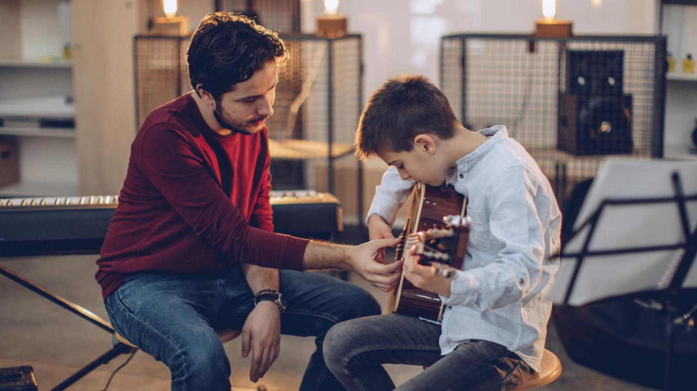 Freiberuflicher Gitarrenlehrer unterrichtet Jungen