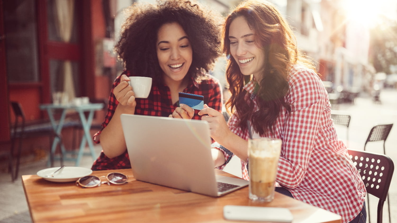 Zwei junge Frauen beim Online Shopping vor einem Laptop in einem Straßencafé