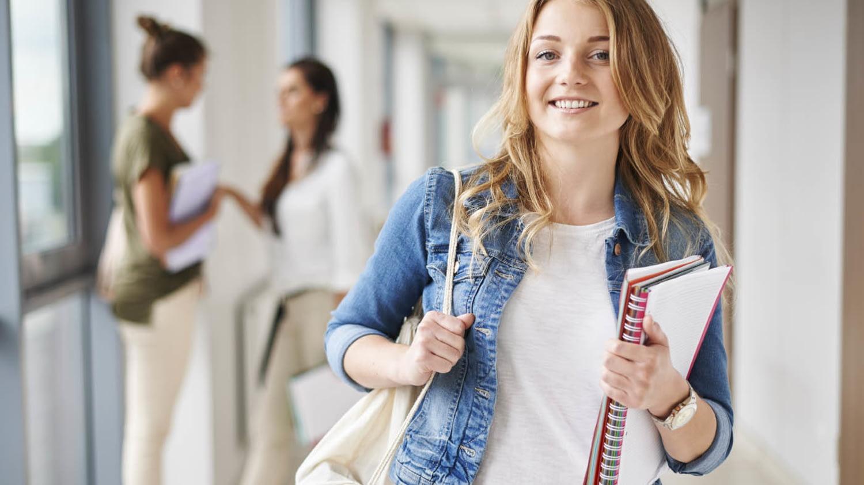Lächelnde duale Studentin mit Unterlagen unter dem Arm im Uniflur