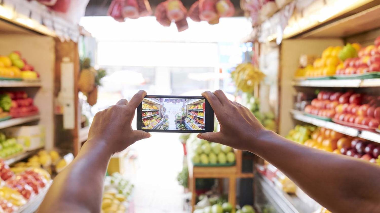 Person fotografiert mit dem Smartphone die Auslagen in der Obst- und Gemüseabteilung