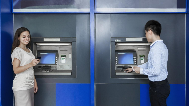 Zwei Personen ziehen an verschiedenen Geldautomaten Geld