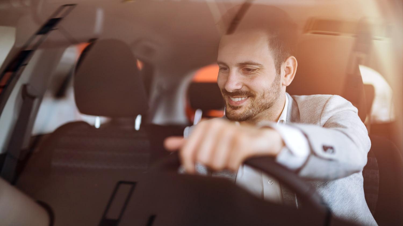 Ein jüngerer Mann im Business-Outfit sitzt gut gelaunt am Steuer eines Autos.