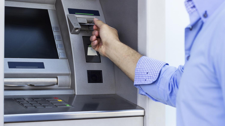 Mann steckt Karte in einen Geldautomaten