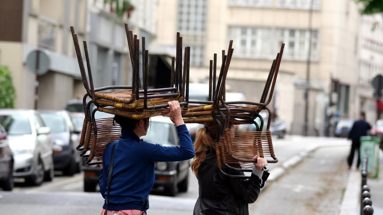 Zwei Personen tragen Stühle über Kopf durch eine Straße