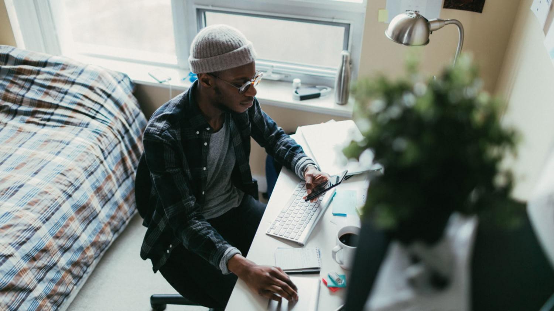 Student arbeitet am Schreibtisch in seinem Wohnheimzimmer