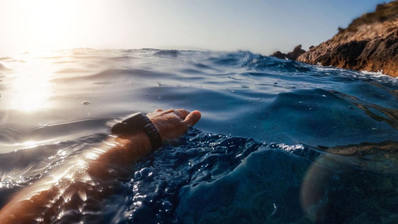 Mensch schwimmt mit Smartwatch im Meer