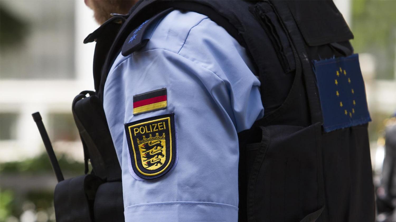 Ein Polizist mit Schutzweste und Walkie-Talkie