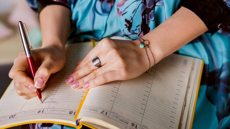 Frau schreibt eine Notiz in ihren Kalender