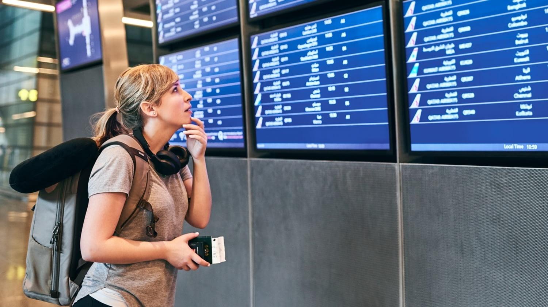 Eine Frau steht vor einer digitalen Anzeige und sucht ihren Flug.