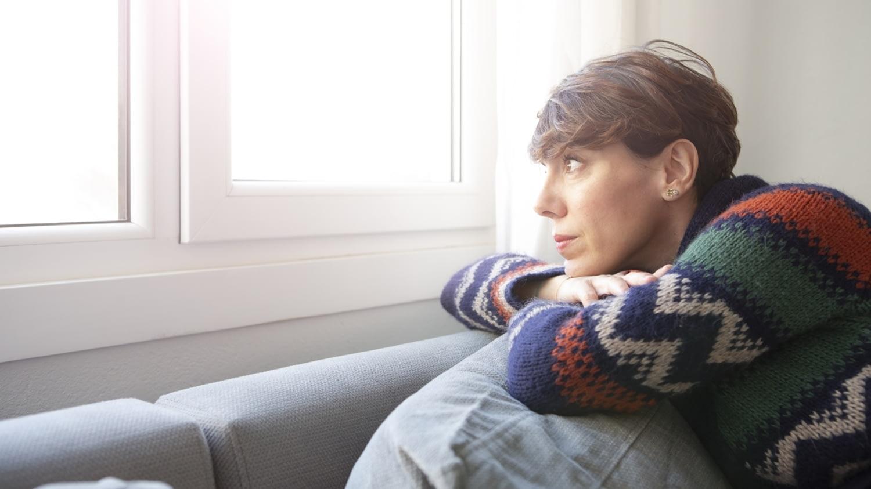 Eine Frau mittleren Alters sitzt auf einem Sofa und blickt melancholisch durchs Fenster nach draußen